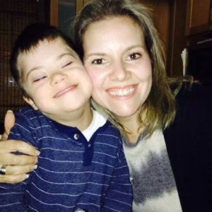 Mother hugging son with Down syndrome, both smiling
