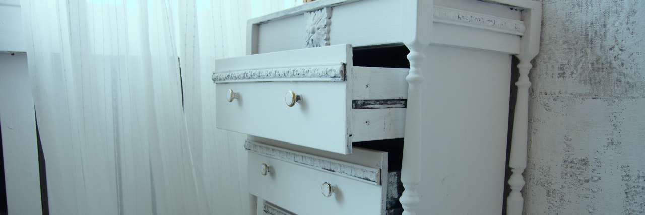 An old painted white ladies chest of drawers with open drawers by the window. Ladies' retro table near the cloth wall