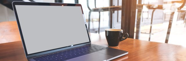 Mockup image of laptop with blank screen on wooden table near by window in modern cafe