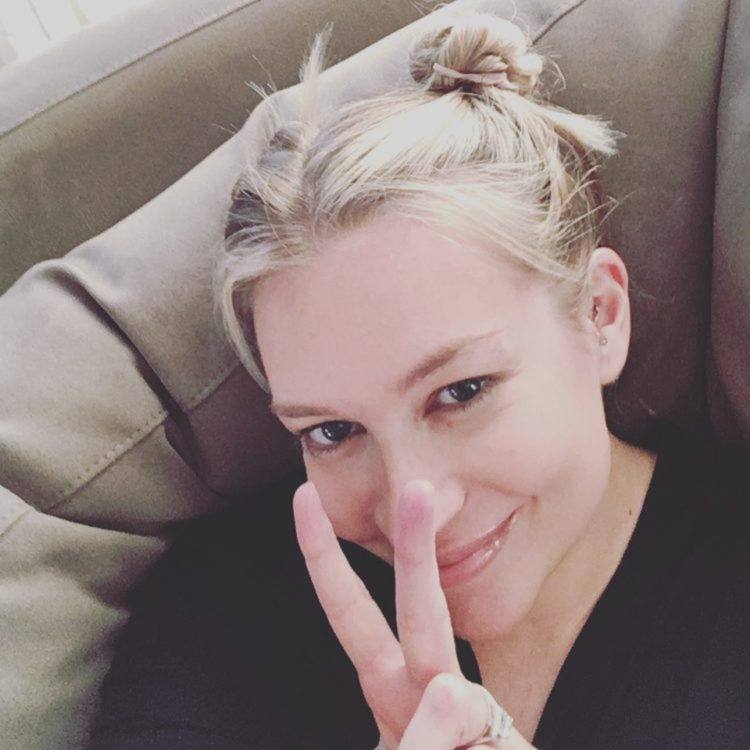 "The writer sitting on a couch, making the ""peace"" sign."