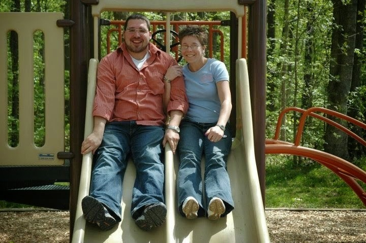 man and woman sitting on a slide at a playground