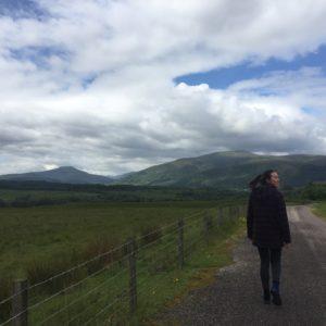 woman walking down a road in scotland