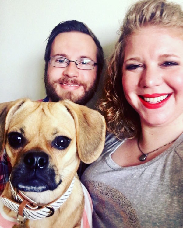 woman smiling with her fiance and dog