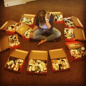 Sadie Williams poses with her Nike shoe boxes full of empty prescription and supplement bottles she has collected over the past 3 years of her fight against Lyme.