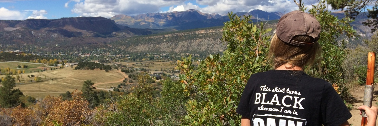woman hiking in the mountains with a black shirt on that says 'this shirt turns black whenever I am in pain'