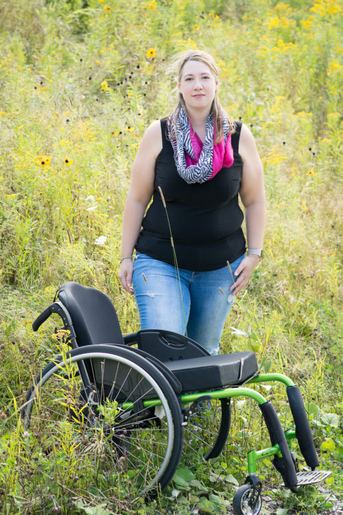 The writer standing in a field of flowers, with her wheelchair in front of her.