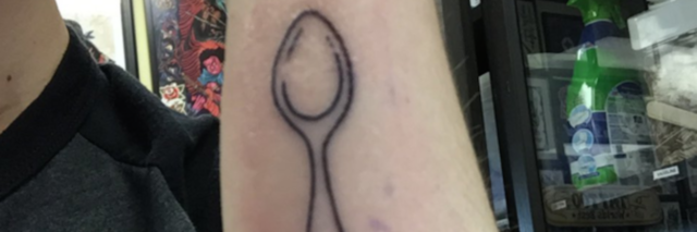 The writer showing her new spoon tattoo on her arm.