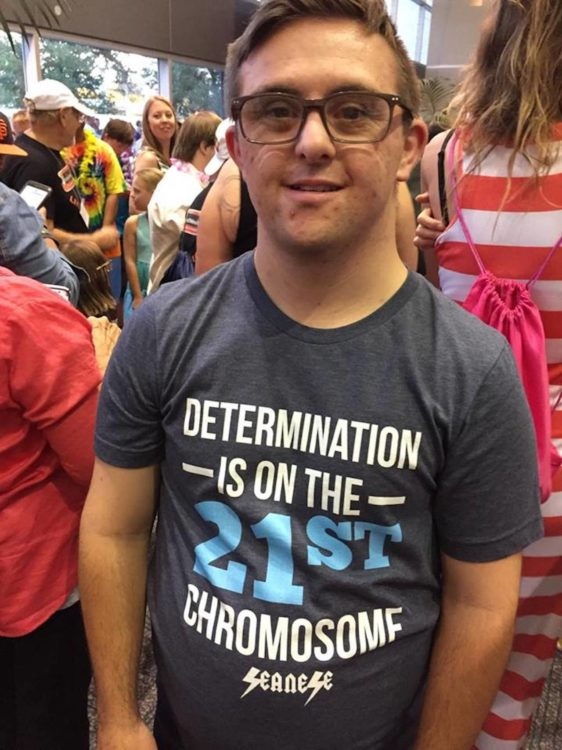 "Sean wearing one of his shirts that reads, ""Determination is on the 21st chromosome"""