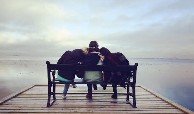 friends sitting on a bench at the end of a pier