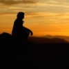 Silhouette of woman sitting on rock, watching sunset
