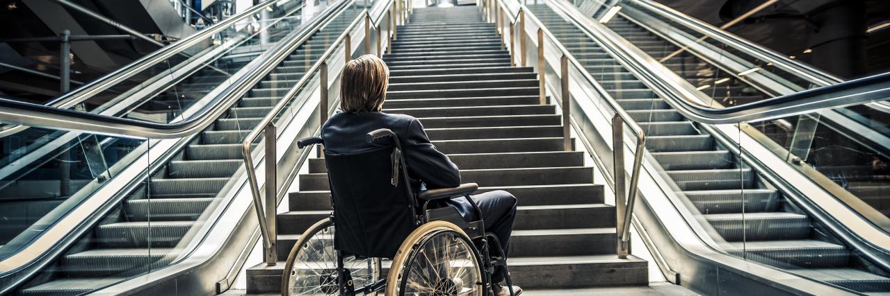 Businessman in a wheelchair against modern stairs.