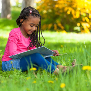 Girl sitting in the grass reading a book.