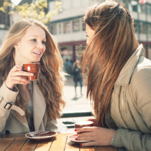 two women chatting in a cafe over coffee
