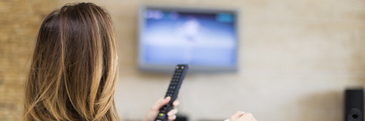 woman watching tv and holding a remote