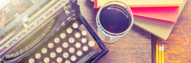 A vintage typewriter with paper, pencils, and a glass of wine next to it.