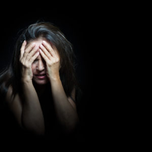 A woman in a dark room, with her hands to her face, crying.