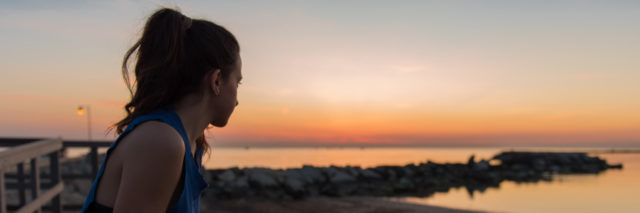 woman looking at the sunrise on a beach