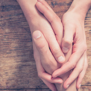 Two people holding hands on wooden table in comforting gesture