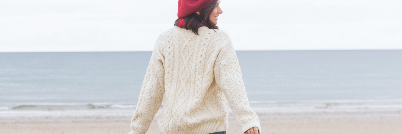 rear view of woman wearing hat and sweater, walking on beach on a cloudy day