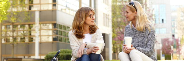 Two women sitting and talking with coffee outdoors
