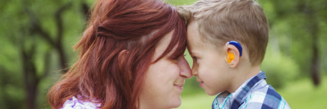 Mother and son forehead to forehead, boy has a hearing aide
