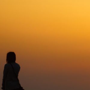 Silhouette of woman in front of sunset sky