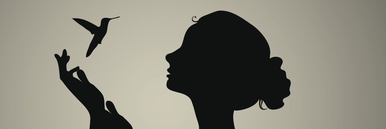 Black silhouette of a woman with a hummingbird.