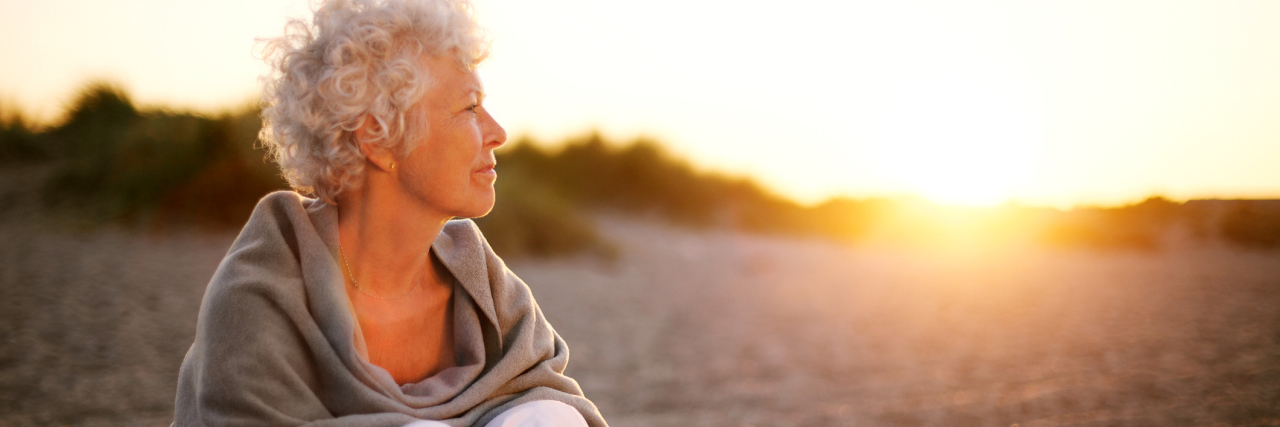 older woman sitting on a beach at sunset