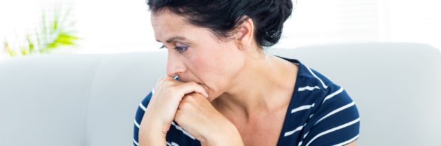 woman sitting on the couch looking worried