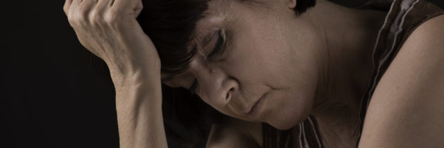 woman leaning her head against her hand and looking upset