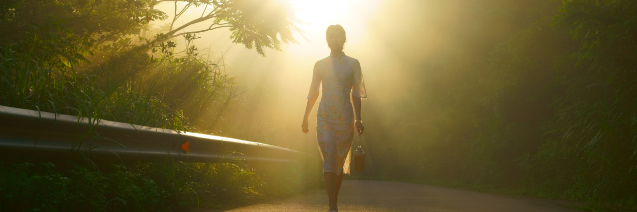 woman walking down a trail between trees with sunlight ahead