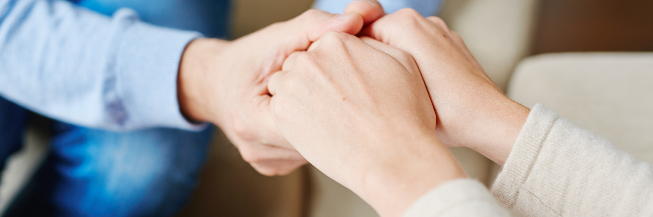 therapist or counselor holding hands with patient close up