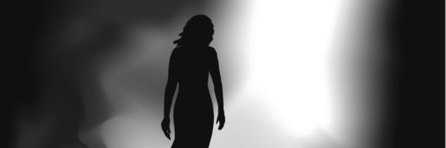 A woman walking from darkness to an entry way of light.