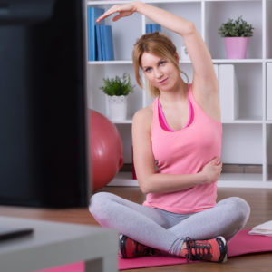 woman doing exercises in front of her tv at home