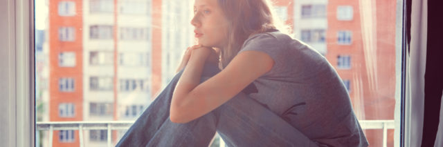 young woman sitting on windowstill looking sad while books sit on table nearby