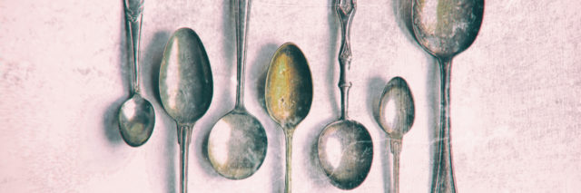 Antique silver spoons on white background.