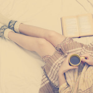Woman on the bed with old book and cup of coffee in hands, top view point. Copy space for text. Soft photo.