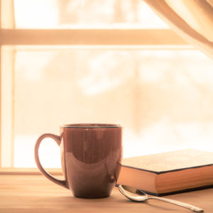 coffee and book sitting on a shelf next to a window