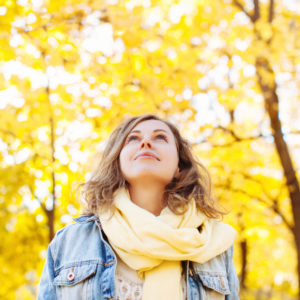 A woman looking up at trees on a fall day
