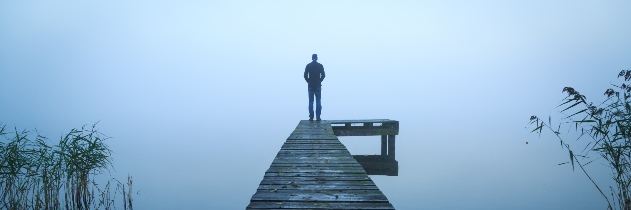 man standing alone on jetty on lake on foggy day