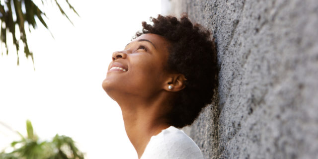 woman leaning against a wall, looking up and smiling