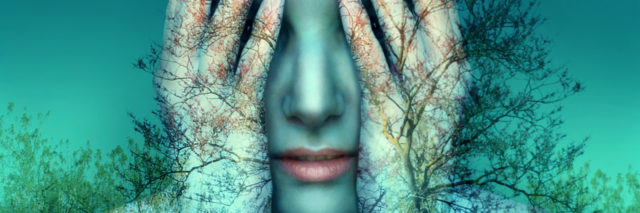 woman covering her eyes with a double exposure of blue trees