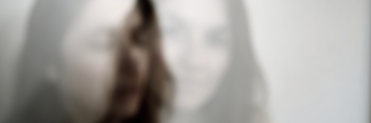 Out of focus multiple exposure portrait of a young Caucasian woman.