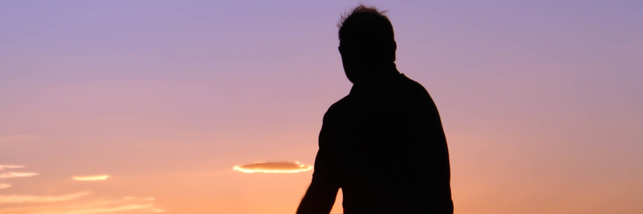 Silhouette of man sitting on rock, facing sunset sky
