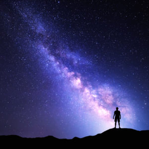 silhouette of a person standing against a starry night sky