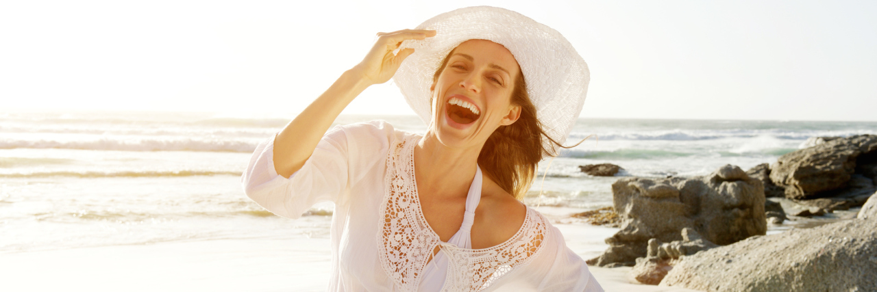 A smiling woman at the beach.