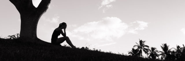 silhouette of woman sitting under a tree