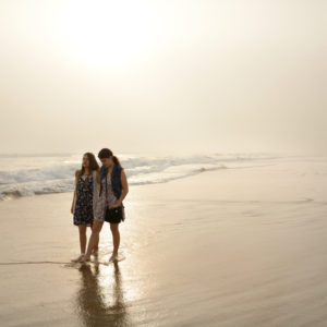 two women walking on foggy beach together