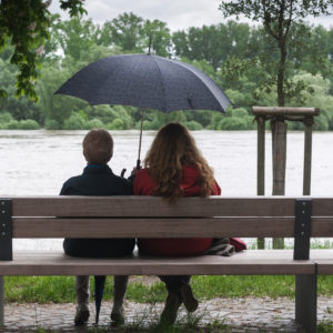 two women sitting on a park bench next to a lake under an umbrella