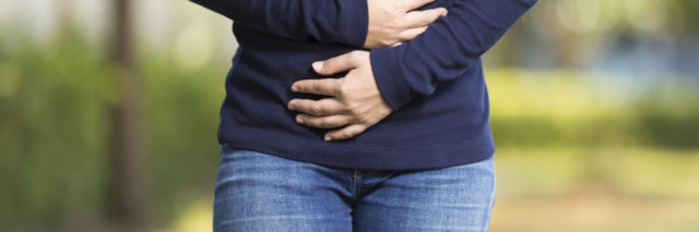 woman in park with stomach ache hands on stomach